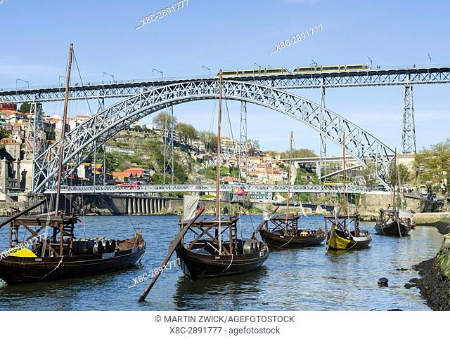 View from Vila Nova de Gaia towards Porto with the old town, the bridge Ponte Dom Luis I and the traditional Rabelo boats, used to ship wine