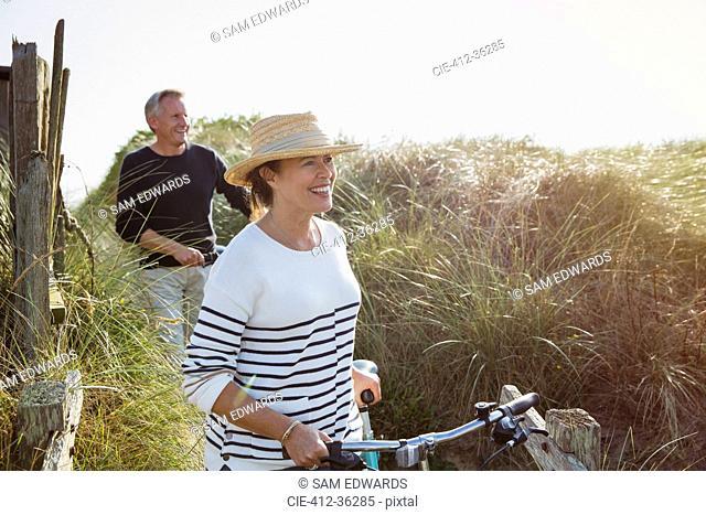 Mature couple walking bicycles along sunny beach grass
