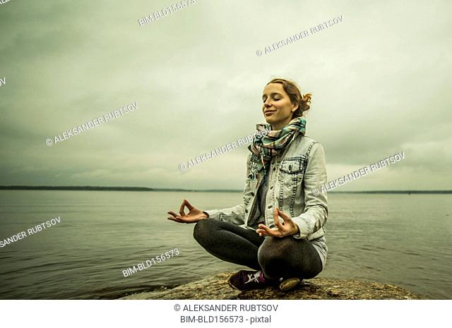 Caucasian woman meditating near ocean