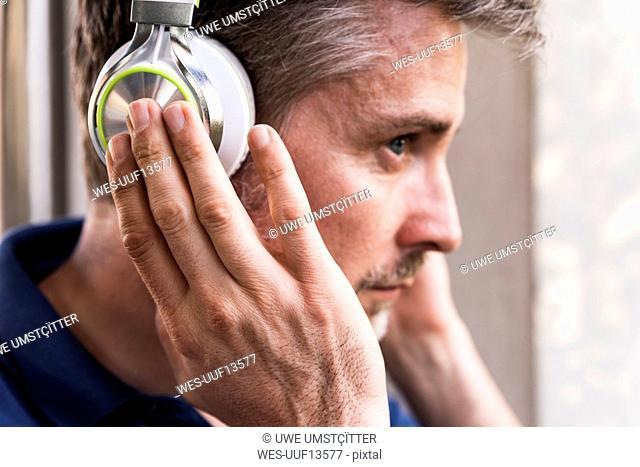 Man listening music with headphones, close-up