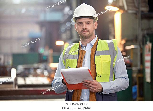 Portrait confident male foreman with clipboard in factory