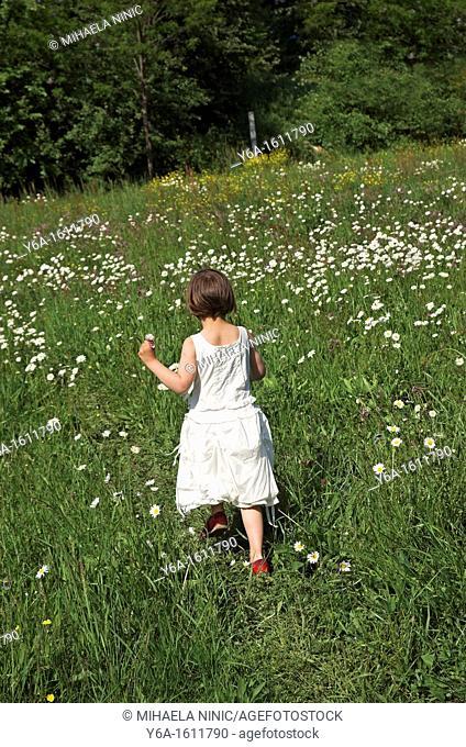 Little girl running across field rear view