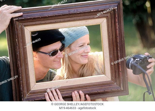 couple in a picture frame taking a photo of themselves