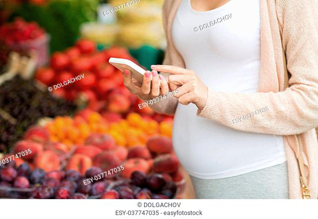 sale, shopping, food, pregnancy and people concept - close up of pregnant woman with smartphone at street market