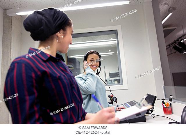 Teenage girl musicians recording music in sound booth