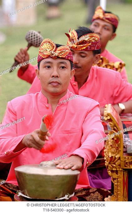 three balinese musicians playing gamelan