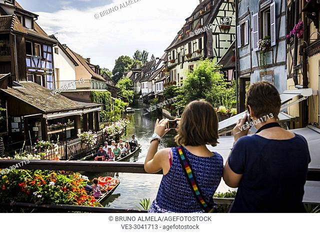 Taking pictures of tourists boat along channel at Little Venice in medieval town of Colmar, Alsace (department of Haut-Rhin, region of Grand Est, France)