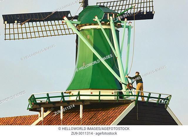 Miller operating windmill, Zaanse Schans a village near Zaandijk in the municipality of Zaanstad, North Holland, Netherlands