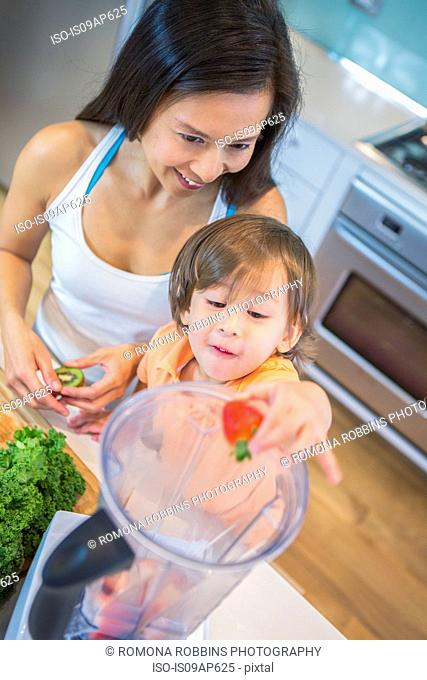 High angle view of male toddler and mother putting strawberries into blender on kitchen counter