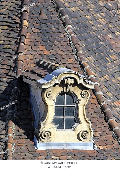 weathered old ornate dormer windows and roof tiles