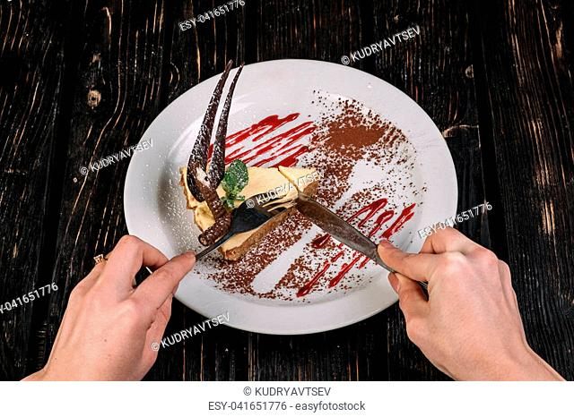 Hands holding knife and fork in front of plate with cheese cake on dark wood background