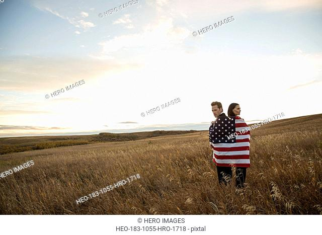 Business colleagues wrapped in American Flag on field