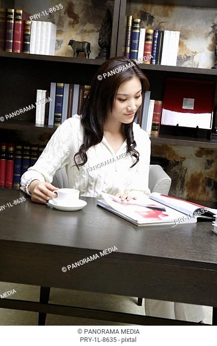 Young woman with coffee cup and magazine