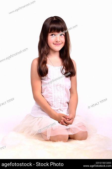 Small girl in angelic costume sitting on white cloud