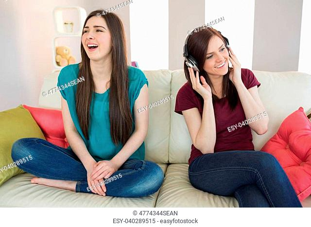 Girl listening to music with her friend beside her on the sofa at home in living room