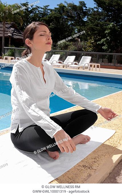 Woman practicing yoga at the poolside