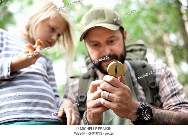 Father showing compass to daughter in forest