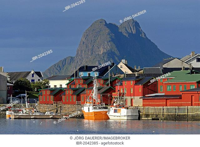 The peaks of Vestvågøy behind the boats and houses of Stamsund illuminated by warm morning light, Nordland, Norway, Europe