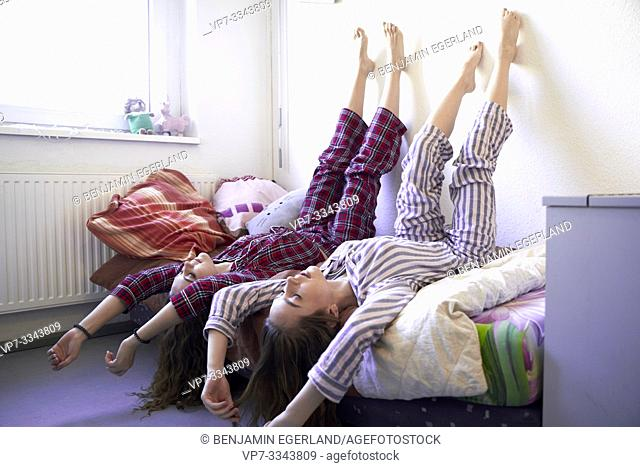 two young women laying upside down in bed together, wearing pyjamas