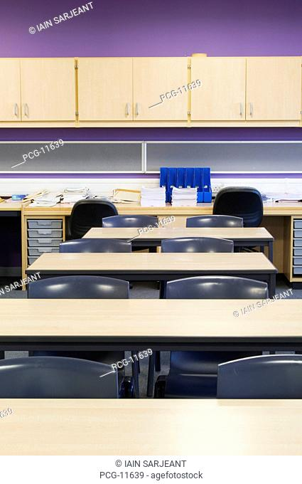 Interior of a classroom in a modern secondary school with desks, chairs and wall mounted cupboards