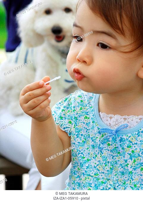 Close-up of a baby girl blowing bubbles with a bubble wand