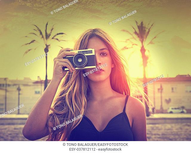 Teen girl with retro photo camera at sunset as a photographer filtered image