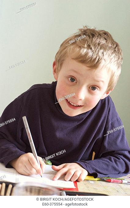 Six year old boy sitting at desk doing homework
