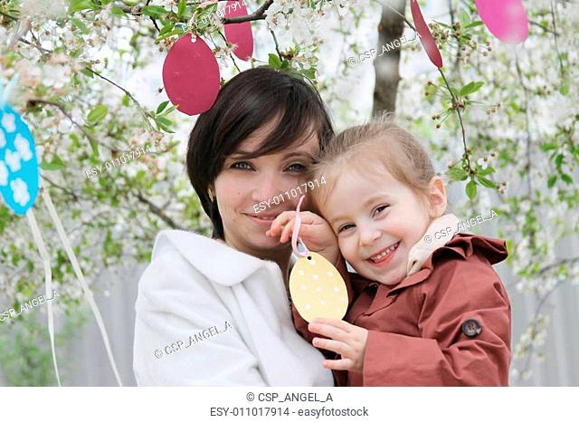 Mother and daughter in blooming garden decorating for Easter