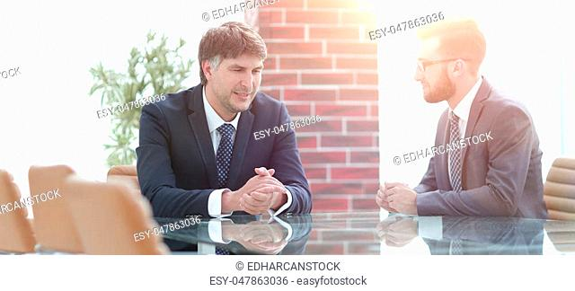 Two businessmen discuss tasks sitting at a table. Business concept