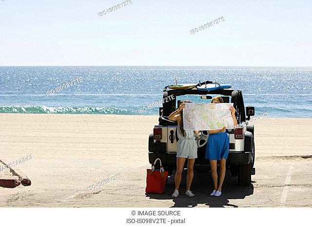 Young women by vehicle, looking at map
