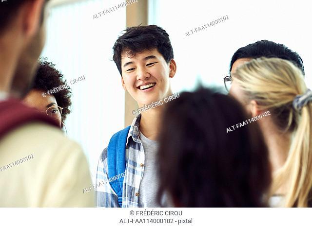 Classmates talking together in corridor