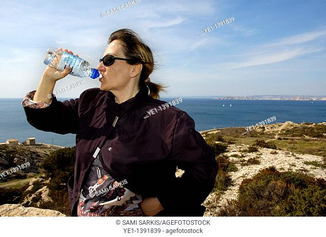 Woman drinking mineral water near the coast of Les Goudes, Marseille, France