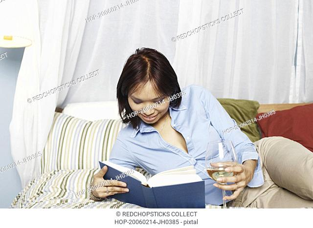 Young woman lying on the bed reading a book