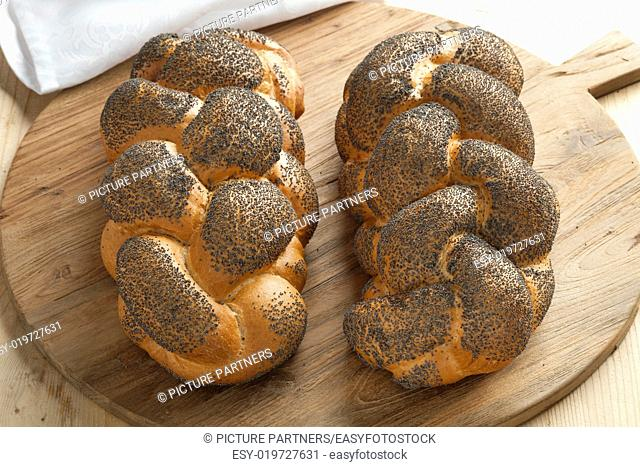 Two whole fresh Challah breads with poppy seeds on a cutting board