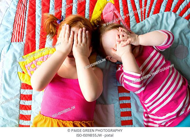 Portrait of two young sisters lying on blanket, covering face with hands