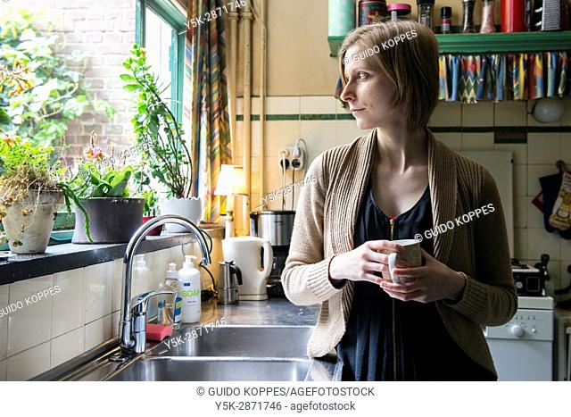 Tilburg, Netherlands. Adult caucasian woman drinking a cup of tea while leaning against a vintage kitchen sink