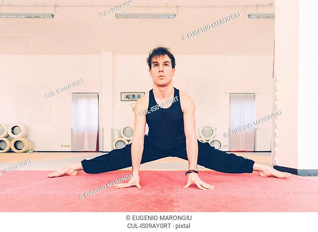 Man legs open, resting on hands doing leg stretching exercises