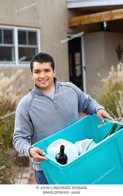 Hispanic man carrying recycling bin