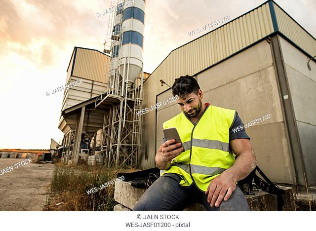 Smiling worker sitting down looking at cell phone