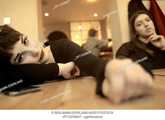 exhausted woman laying on table in restaurant next to friend, in Germany