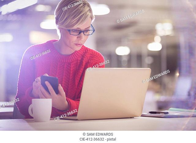 Serious businesswoman working late, using cell phone at laptop in office