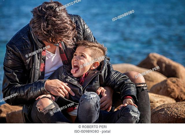 Father and son outdoors, fooling around, sitting on rocks beside sea