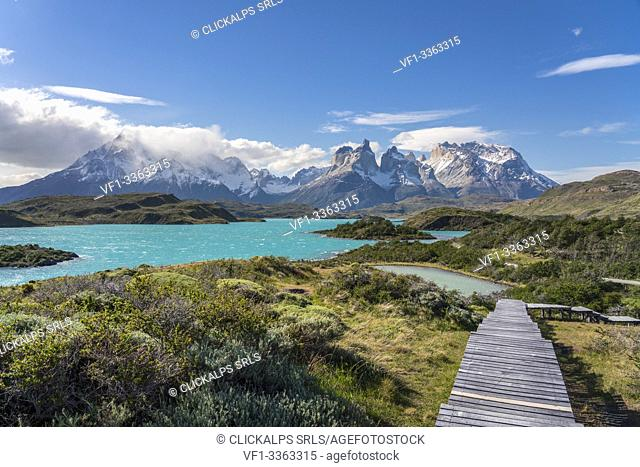 Boardwalk with Lake Pehoé and Paine Horns in the background, on a windy summer day. Torres del Paine National Park, Ultima Esperanza province, Magallanes region