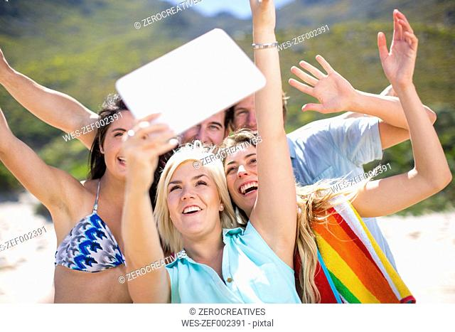 Friends taking selfies with a tablet on the beach