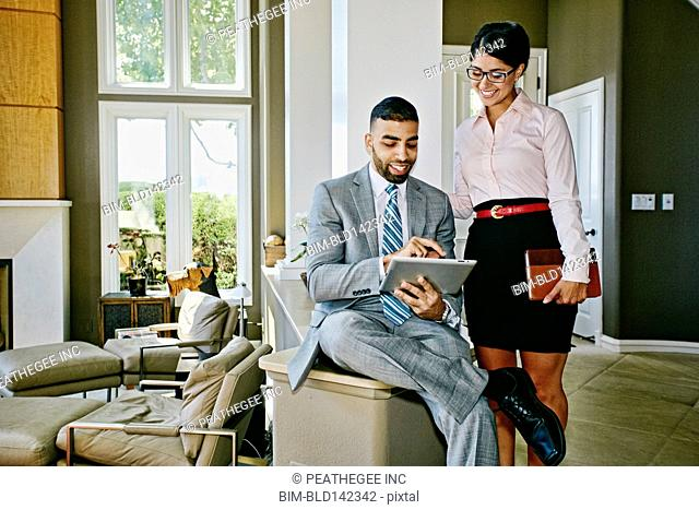 Business people using digital tablet together at home