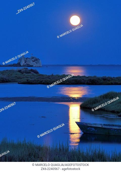 St. John tower ruins and small fishing boat under full moon at Alfacs Bay. Ebro River Delta Natural Park, Tarragona province, Catalonia, Spain