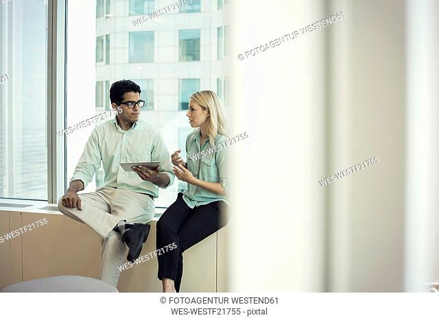 Business people with digital tablet sitting on window sill, discussing