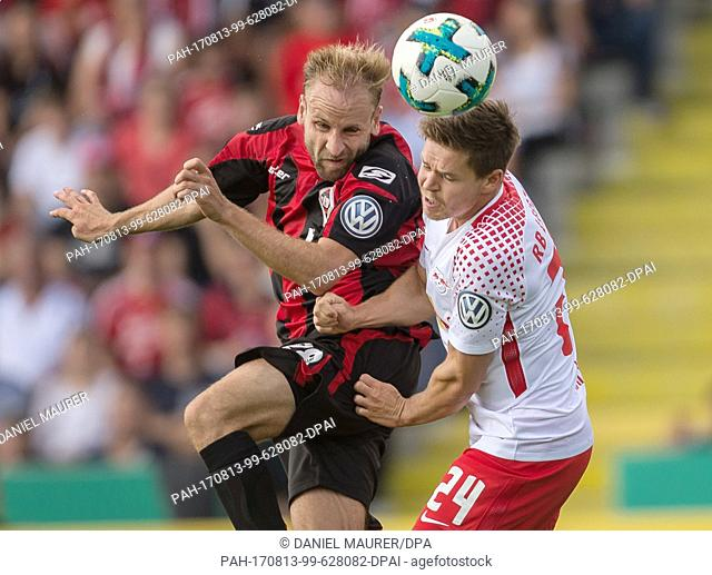 Dorfmerkingen's Carls Murphy (L) and Leipzig's Dominik Kaiser vie for the ball during the German Football Association (DFB) Cup first-round match between...