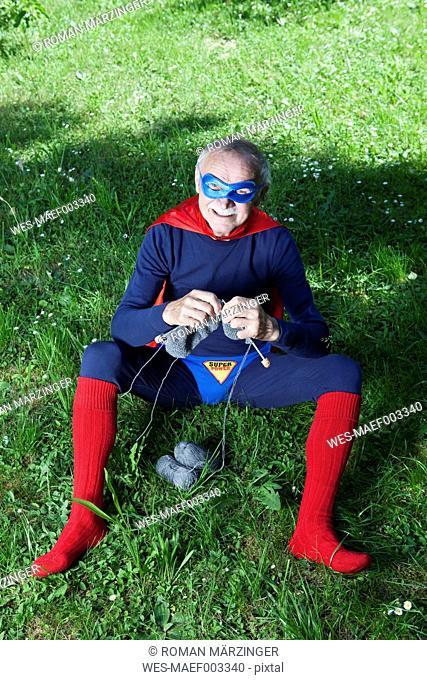 Austria, Burgenland, Senior man in superman's costume sitting on grass and knitting