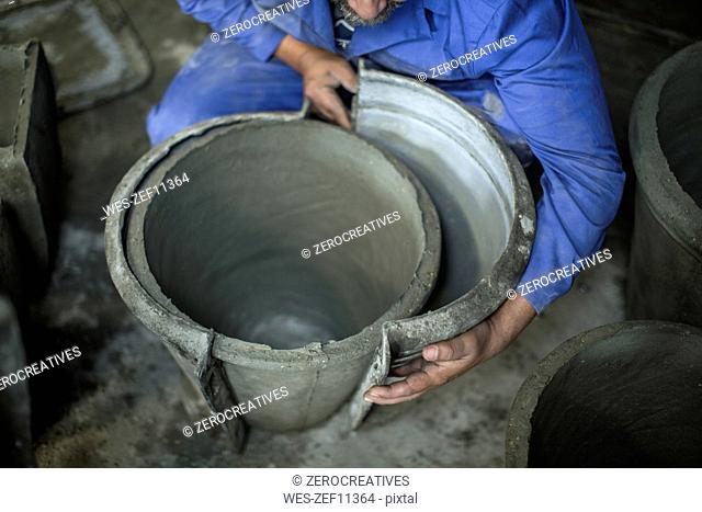 Man opening mold in industrial pot factory
